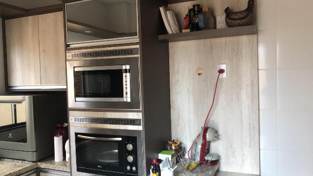 Cozinha planejada com  coifa, forno elétrico, cooktop e microondas